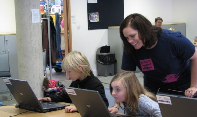 Caius Fellow Dr Michelle Ellefson supports two children on laptop computers