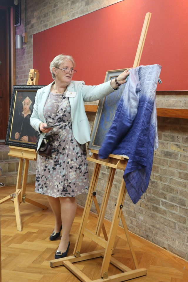 The Master unveiling the new portrait, starting to move a blue cover to uncover the portrait.