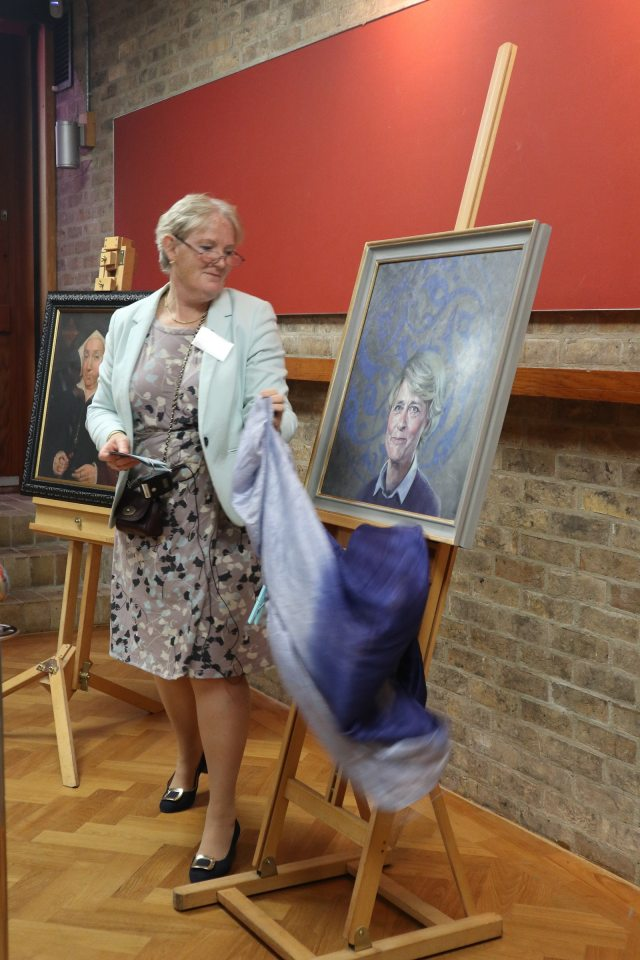 The Master moving a blue cover to unveil the full portrait.