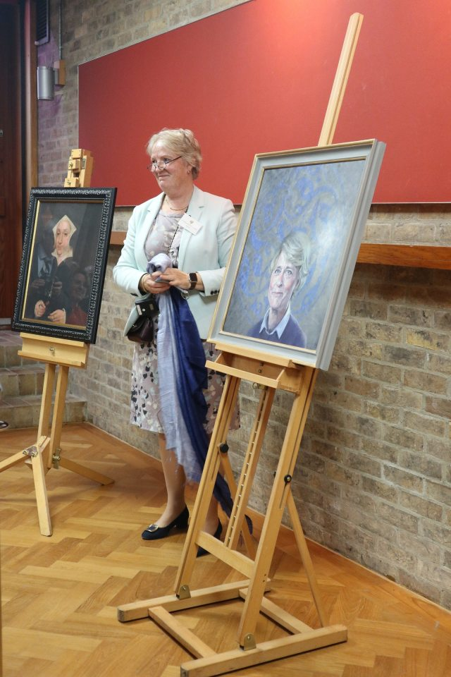 The Master standing next to the portrait, having just unveiled the portrait. The full portrait is now visible, sitting on a wooden easel.