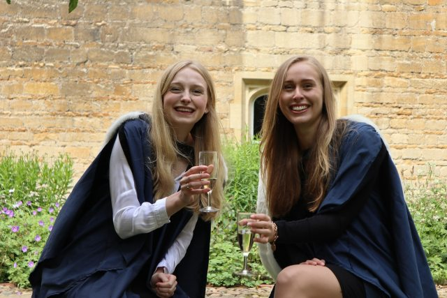 Two female graduates celebrate with a glass of champagne