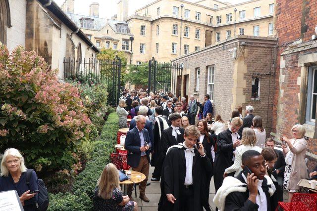 People walking along a narrow path between buildings