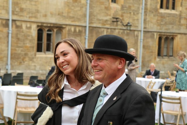 A female and a male in a bowler hat pose for a photo