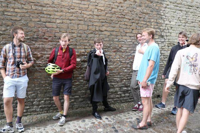 Six men near a wall